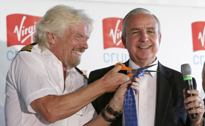 Richard Branson, founder of the Virgin Group, left, laughs as he cuts the tie of Miami-Dade County Mayor Carlos Gimenez, Tuesday, June 23, 2015, at Perez Art Museum in Miami, after a news conference where it was announced that Virgin Cruises will set sail from PortMiami in 2020. (AP Photo/Alan Diaz)